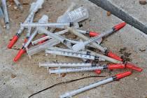 Strážníci sbírají injekční stříkačky po narkomanech.