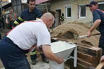 Hasiči ucpávají pytli s pískem umělou hráz říčky Litavy u Měnína na Brněnsku.