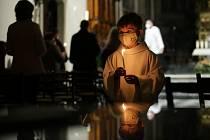 Mladí ministranti roznášejí oheň zpaškálu věřícím vkatedrále.