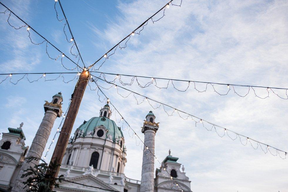 STŘECHA SVĚTEL. Vánoční trhy u Karlsplatzu ve Vídni zastřešily provazy světel. Pod katedrálou řádily děti, do vzduchu vyhazovaly slámu.