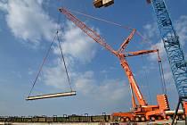 Autojeřáb  začal 25. dubna 2020 odstraňovat nosníky starého mostu na silnici první třídy přes Novomlýnské nádrže.