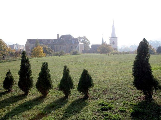 Na místě plánovaného parku v Útěchově teď parkují auta, ale porostou tam stromy. V Komíně je místo vzrostlého parku zatím jen tráva a túje.