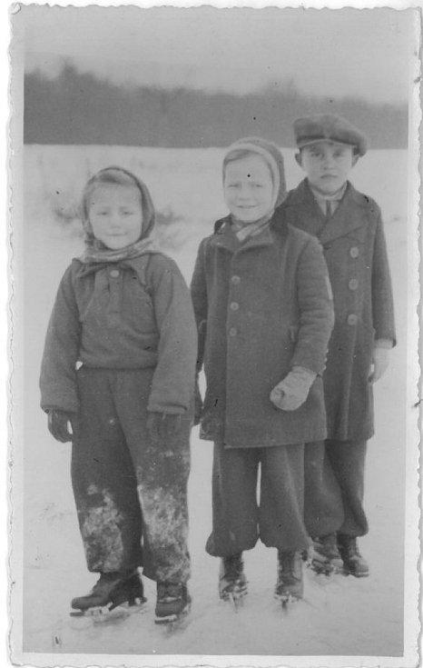 Břeclav. Tři děti v zimě na bruslích na ledu. Uprostřed je syn autora fotografie, Jan Janošek a vpravo Jan Pražák – 40. léta 20. století.
