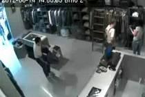 Jeden ze zlodějů ukradl značkovou bundu, zatímco jeho komplic zabavil prodavačku.