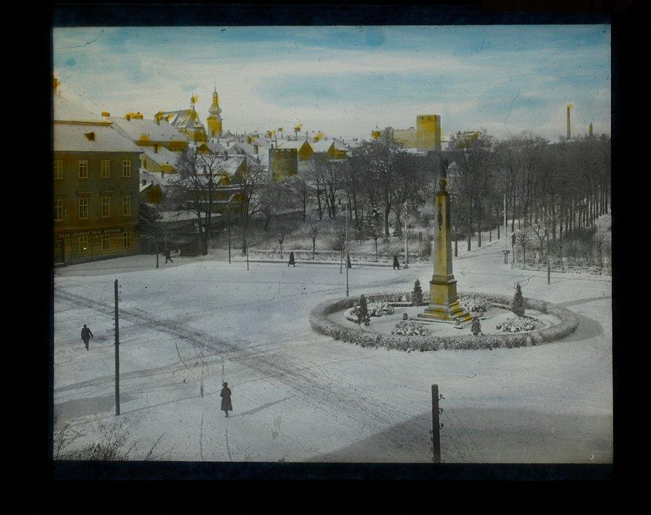 Celkový pohled na Komenského náměstí ve Znojmě s Kopalovým pomníkem a Husovými sady v pozadí v zimě. Zachycena i budova Nové lékárny (1918-1938).