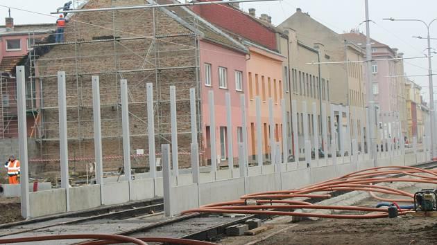 Dělníci staví kolem nové tramvajové tratě na Plotní vysoké a betonové protihlukové stěny.