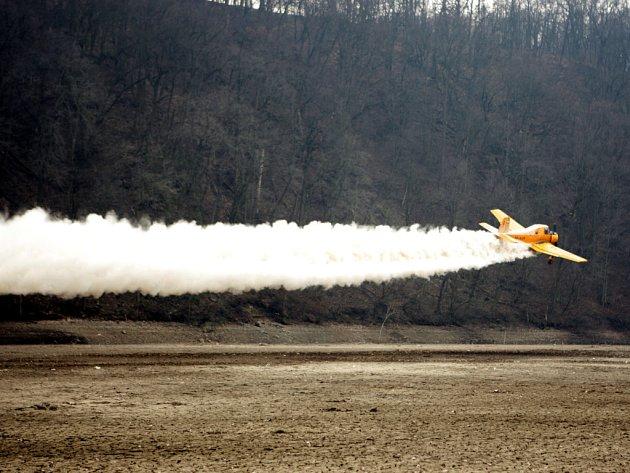 Letadla rozprašují vápenec nad brněnskou přehradou.