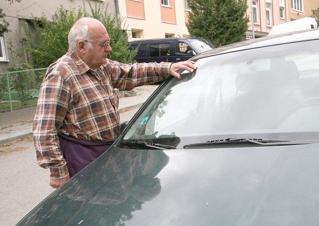 Pan Macík ukazuje poškození svého auta