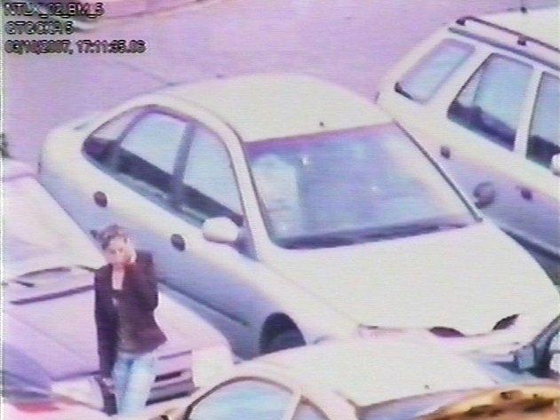 Neznámá pachatelka obhlíží parkoviště. Záběr z průmyslové kamery.