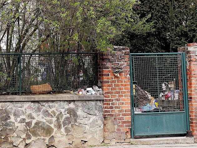 Odpadky se na ženině zahradě povalují všude. I na chodníku, který vede ke dveřím do domu.