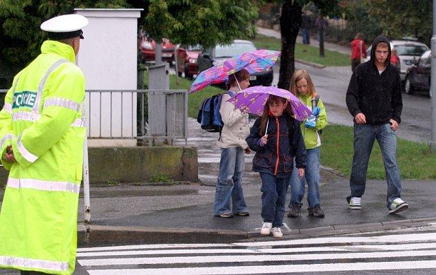 děti přecházejí ulici pod dozorem policistů