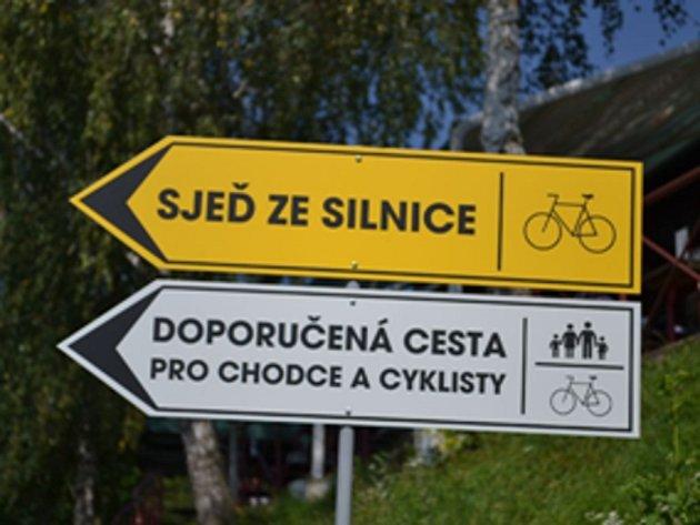 Značka u přehrady vede cyklisty na úzkou stezku pro pěší.