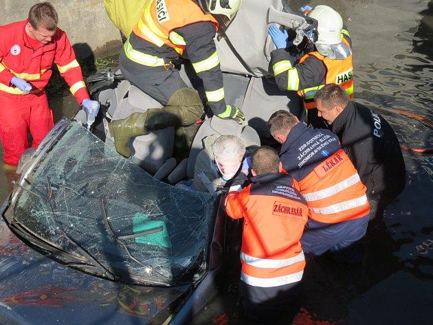 Auto převrácené na střechu potopené střechou do bahna. Řidič v něm zůstal připoutaný k sedadlu. A zraněný.
