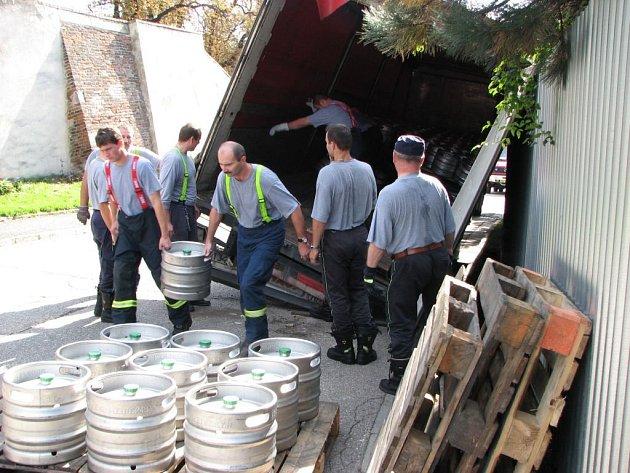 Hasiči vytahují pivní sudy z havarovaného kamionu.