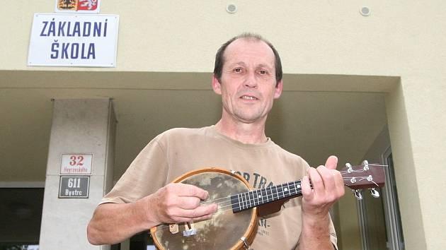 Šedesátiletý Bohumil Pokorný hraje žákům při cestě do školy v brněnské Heyrovského ulici na ukulele.