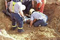Záchranáři vyprošťují zavaleného dělníka, který zahynu poté, co se na něj sesunuly tuny hlíny