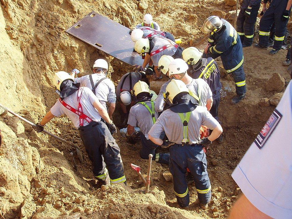 Záchranáři vyprošťují zavaleného dělníka.