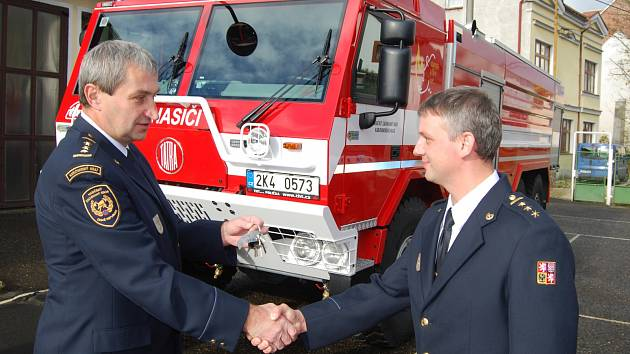 Velitel kraslických profesionálních hasičů Petr Hamouz (vpravo), přebírá klíče k nové Tatře od ředitele krajských hasičů Václava Klemáka