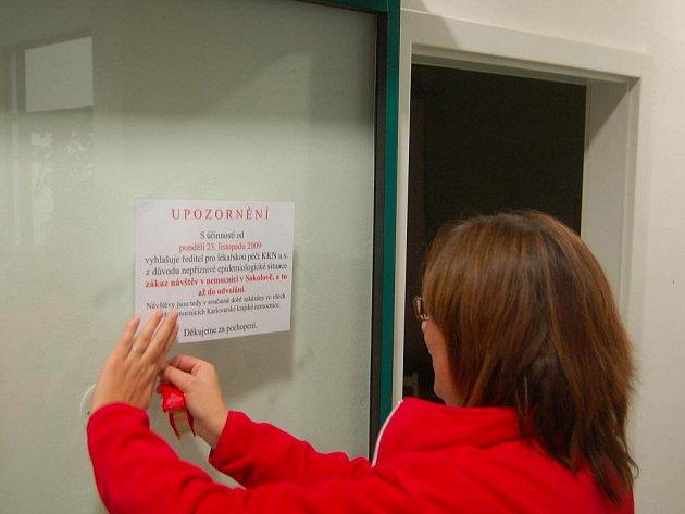 Zaměstnankyně centrálního příjmu sokolovské nemocnice, vyvěšuje oznámení o zákazu návštěv.