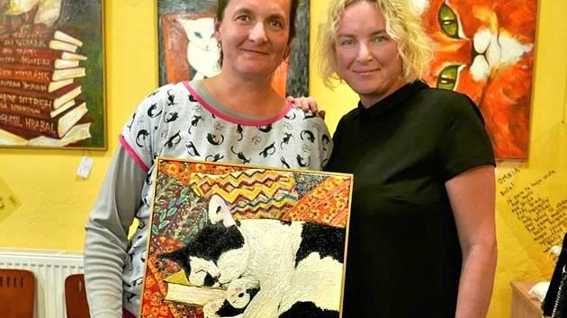 Na snímku vlevo majitelka kočičího útulku Konec toulání a malířka Romana Štrynclová s obrazem, který se vydražil za rekordní sumu.