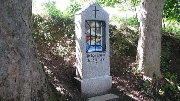 V okénku je umístěný svatý obrázek s podobným motivem, který tu původně býval. Na kameni je pak vytesaný německý nápis Heilige Maria bitte für uns.