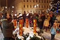 Kraslice rozsvítí poslední svíci na obřím adventním věnci.