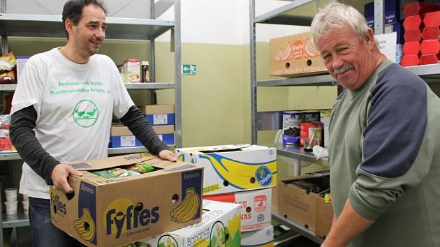 Dobrovolníci v potravinové bance, včetně ředitele Milana Hlouška, zboží třídili a ukládali do regálů.