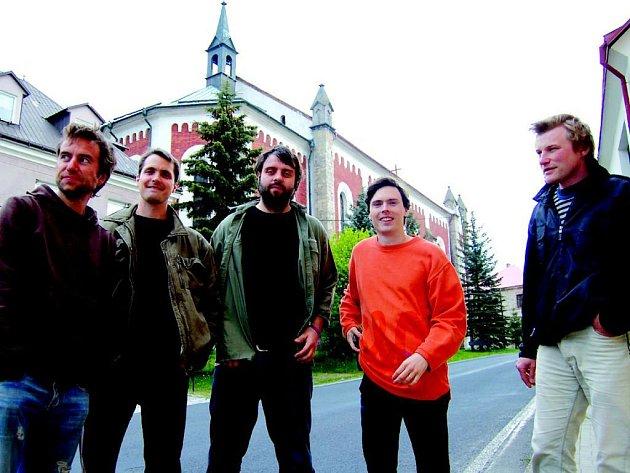 Členové skupiny Tata Bojs pózují před kostelem v Krásně.