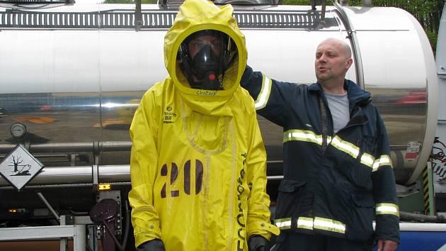 Jeden z hasičů si zkouší speciální protichemický oblek s dýchacím přístrojem.