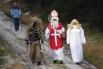 Mikuláš s andělem a čertem přicházejí ke kostelu pod horou Krudum.