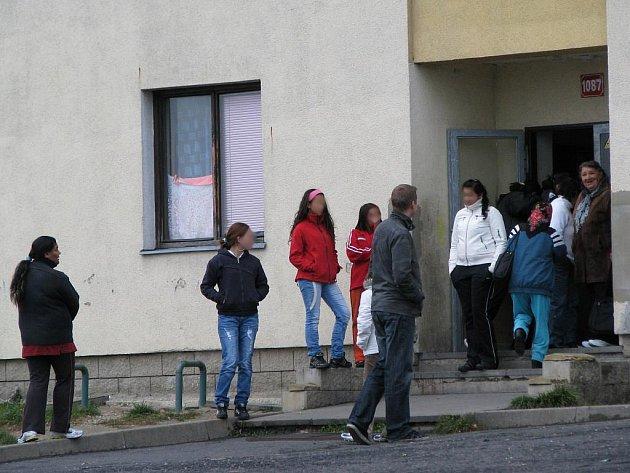Lidé před domem čekají na odvoz. Prý dostanou zaplaceno, když půjdou volit.