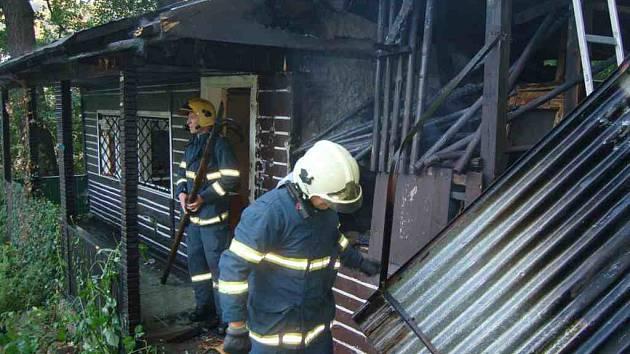Hasiči v Lokti likvidují požára zahradní chatky.
