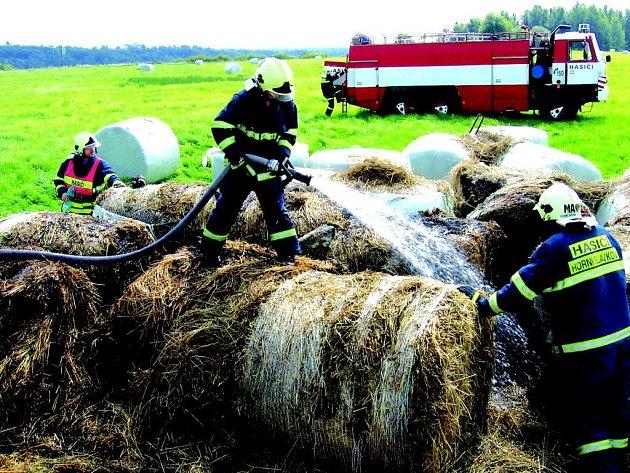 Slavkovští hasiči likvidují požár balíků slámy.