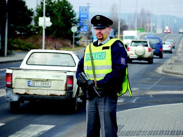 Policista ozbrojený samopalem hlídá jednu z hlavních silnic směrem z města.