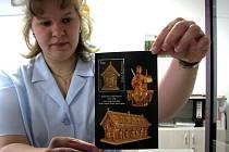 Poštovní úřednice ukazuje aršík s jednou známkou s motivem relikviáře sv. Maura.