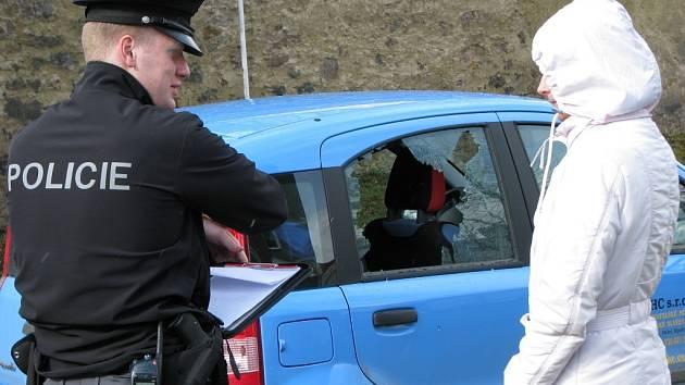 POLICISTA sepisuje na místě prvotní informace s poškozenou.