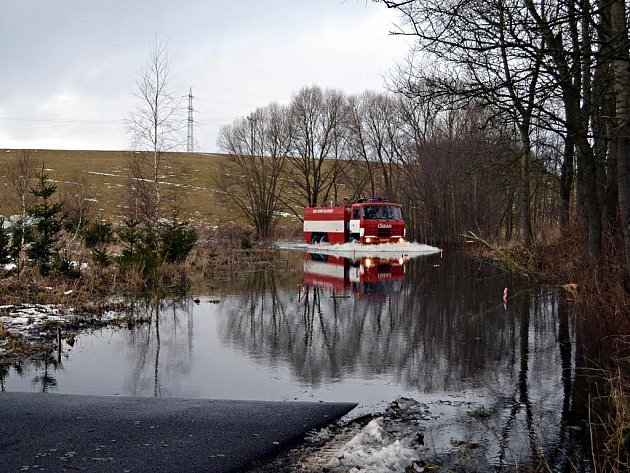 Hasiči několikrát denně projíždí zaplavenou silnici v Bošířanech na Sokolovsku, aby si byli jistí, že lagunou projedou v případě nouze.