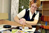 VELIKONOČNÍM RAZÍTKEM začala tisknout pošta v Kraslicích. Letos má nový motiv – kohouta s malovanou kraslicí. Na snímku tiskne vedoucí pošty Iva Vlčková. Psaní putují do celého světa.