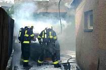 Auto začalo v Chodově hořet na zahradě mezi dvěma domy.