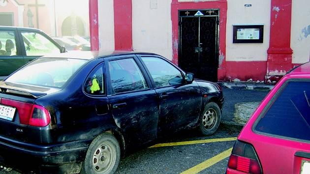 Parkování před kaplí zakazuje žlutá vodorovná dopravní značka.
