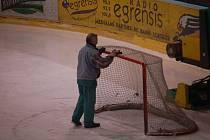 Konec. Ledař uklízí hokejovou branku.