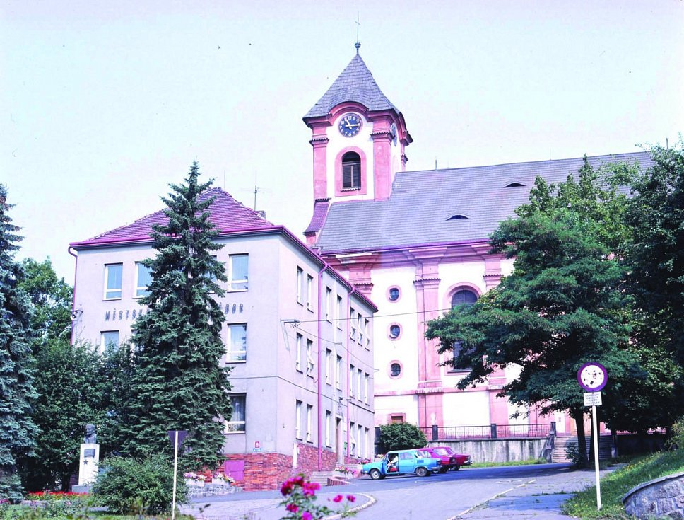 MĚSTSKÝ NÁRODNÍ VÝBOR se sochou Vladimíra Iljiče Lenina, v pozadí kostel Sv. Vavřince. Za povšimnutí stojí i dobový vozový park.