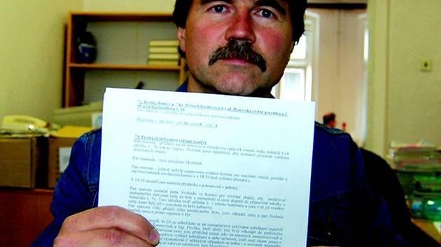 Jiří Srkjov drží v ruce usnesení zastupitelstva, na kterém se rozhodovalo o prodeji bytů.