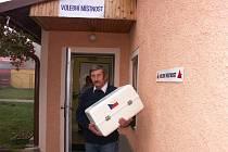 Člen volební komise Tomáš Hrabák vychází  s volební urnou z Obecního úřadu v Josefově k voličům.
