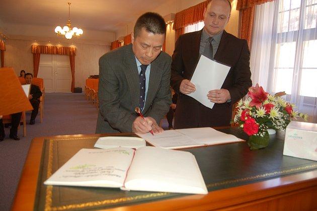 SLAVNOSTNÍ SLIB složil Nguyen Thanh Binh  v obřadní síni Městského úřadu v Kraslicích v doprovodu matrikářky a tajemníka Viktora Semráda (v pozadí).