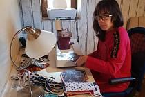 Lucie Gregorová pomáhá se šitím a žehlením roušek.