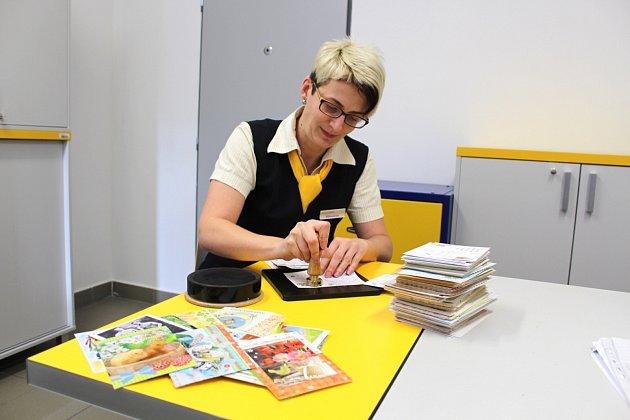 Velikonoční pošta míří do koutů celého světa. Jen za první den označily pošťačky 42,5 kg psaní. Na snímku tiskne vedoucí pošty Iva Vlčková.