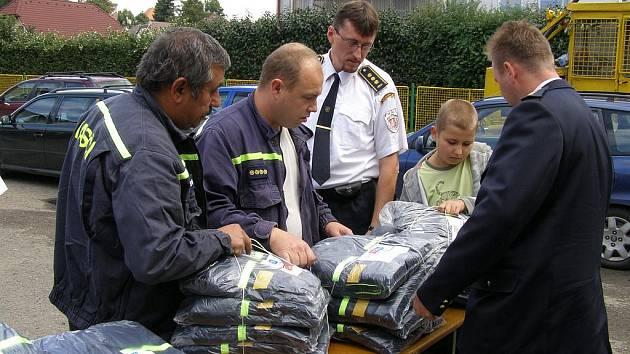 ZÁSTUPCI DOBROVOLNÝCH hasičů z Karlovarského kraje odvezli na sever Čech stejnokroje, které byly původně určené jim. Celkem jich předali 250.