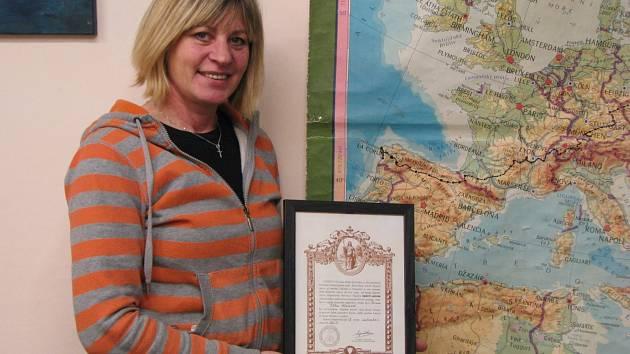 JITKA Hlavsová ve své kavárně v Lokti. S osvědčením o vykonání pouti a mapou, co dostala od přátel. Trasa její pouti je tam černě vyznačená.