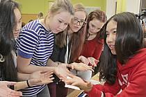 Yichen Cheng (vpravo) ukazuje chodovským studentům gymnázia akupresurní body na dlani
